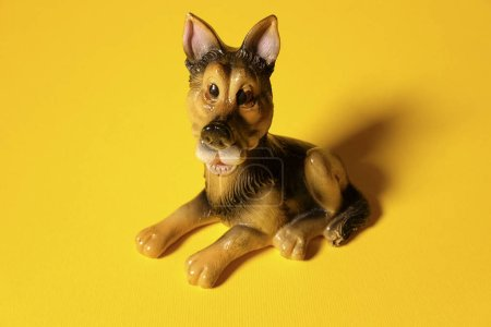 toy dog on a yellow background, little puppy