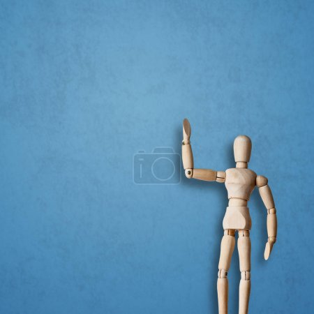 Wooden Mannequin posing on blue background
