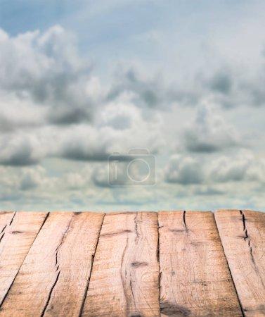 Foto de Tablones de madera texturizados sobre un fondo de nubes borrosas - Imagen libre de derechos
