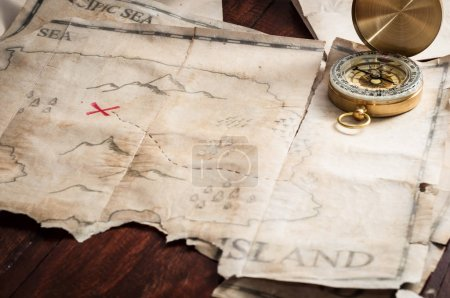 Compass and maps of island with treasure sign