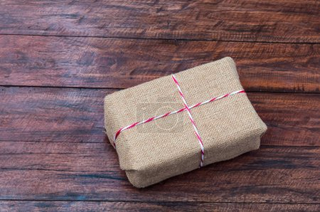 Present box wrapped in sackcloth with colorful ribbon on wooden background