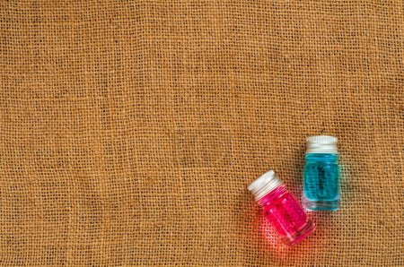 two bottles with blue and pink liquids on bagging background