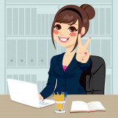 Successful businesswoman making victory hand sign at his office while working typing on laptop on his desk