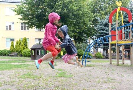 Photo pour Deux sœurs sautent, se tenant la main. Aire de jeux - image libre de droit