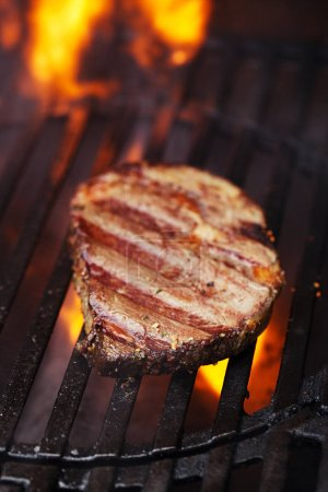 ribeye beef steak on barbecue grill with flame