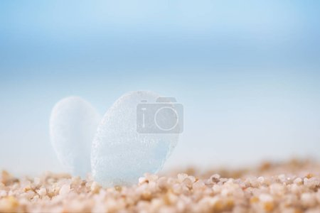 clear sea glass on beach sand with seascape background