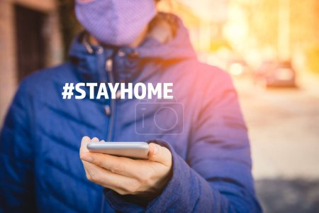 Photo for Stay home hashtag quarantine motivation concept. Quarantine (isolation) reduce contact with potentially infected person in times of epidemic. Woman with smart phone. - Royalty Free Image