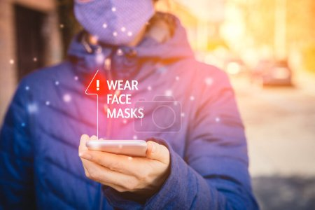 Photo for Wear face masks recommendation. Person with smart phone walk on street and look on wear masks notification on his mobile in pandemic times. - Royalty Free Image