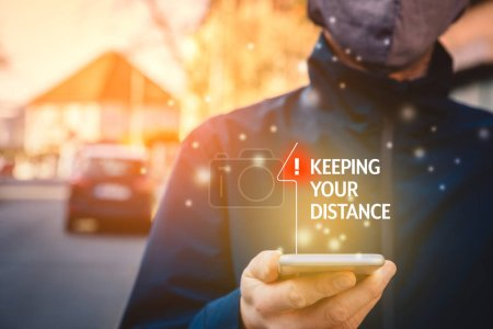 Photo for Keeping distance recommendation on smart phone as notification. Social distance is a recommendation during an epidemic times. - Royalty Free Image