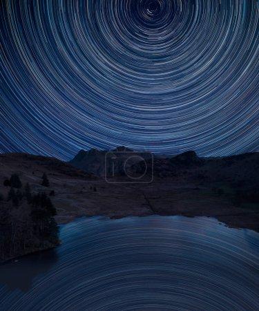 Photo pour Image composite numérique des sentiers étoilés autour de Polaris avec le drone Stunnnig image aérienne du paysage du lever du soleil de Blea Tarn - image libre de droit