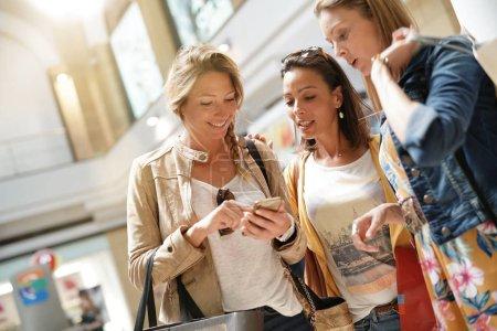 Photo pour Les filles dans le centre commercial en utilisant un smartphone - image libre de droit