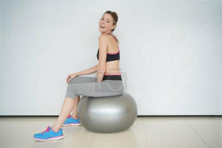 Woman at the gym relaxing on fitness ball