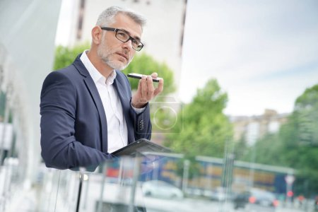 Businessman standing in the street talking on phone