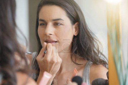 Brunette woman in front of mirror applying lipstik...
