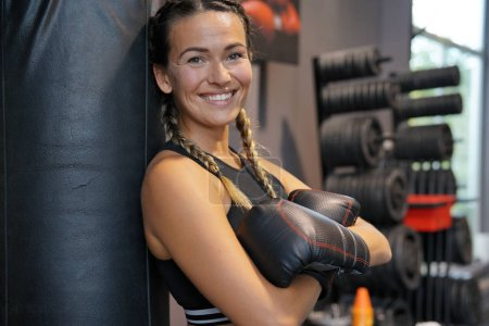 Photo for Woman wearing boxing gloves leaning on a punching bag - Royalty Free Image