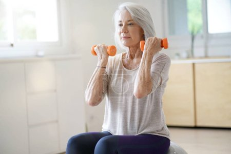 Photo for Attractive elderly woman exercising at home with swiss ball - Royalty Free Image