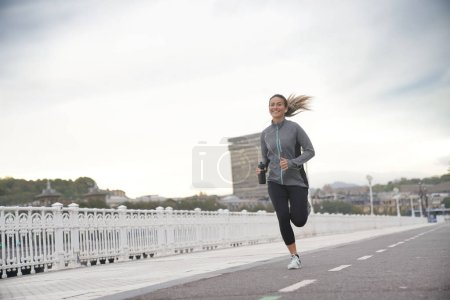 Photo pour Une femme heureuse en courant dans une ville - image libre de droit