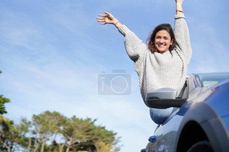 Joyful brunette sitting outside of car window