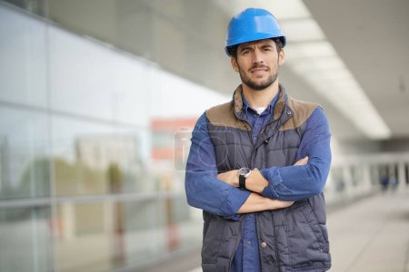 Photo pour Ouvrier industriel de sourire dans le casque devant le bâtiment moderne - image libre de droit