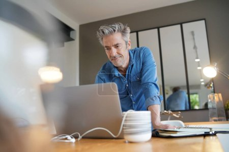 Photo for Mature man working from contemporary home - Royalty Free Image