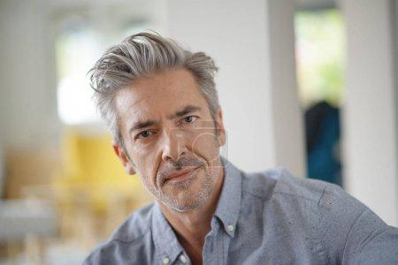 Photo pour Portrait d'un bel homme mature regardant la caméra dans la maison contemporaine - image libre de droit