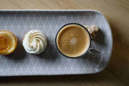 Top view of long plate serving coffee and three delicious mini desserts