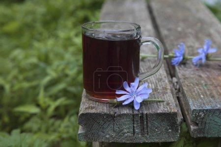 Tasse Chicorée trinken auf dem Rand des hölzernen alten Hintergrund im Garten. Rustikales Stillleben