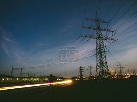 Photo for Electricity pylons at sunset transporting clean renewable energy - Royalty Free Image