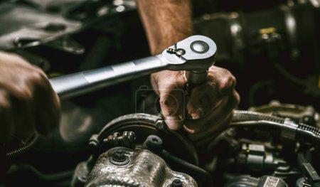 Photo pour Mécanicien automobile travaillant sur le moteur de voiture dans le garage mécanique. Service de réparation. Plan rapproché authentique . - image libre de droit