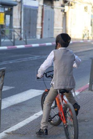 Ultraorthodox Jewish kids riding a bike in the str...