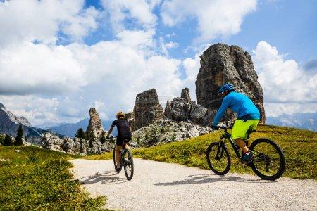 Photo pour Cyclisme touristique à Cortina d'Ampezzo, superbe Cinque Torri et Tofana en arrière-plan. Femme et homme chevauchant le sentier VTT. Tyrol du Sud province d'Italie, Dolomites . - image libre de droit