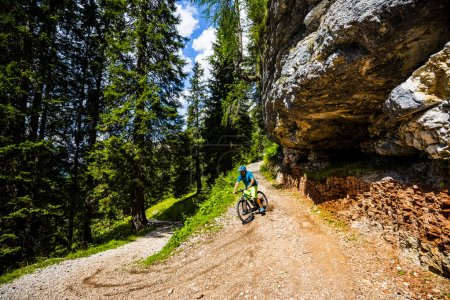 Photo for Tourist cycling in Cortina d'Ampezzo, stunning rocky mountains on the background. Man riding MTB enduro flow trail. South Tyrol province of Italy, Dolomites. - Royalty Free Image