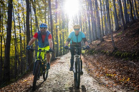 Photo for Cycling woman and man at Beskidy mountains spring forest landscape. Couple riding MTB enduro track. Outdoor sport activity. - Royalty Free Image