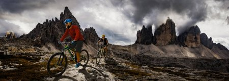 Photo for Cycling woman and man riding on bikes in Dolomites mountains andscape. Couple cycling MTB enduro trail track. Outdoor sport activity. - Royalty Free Image