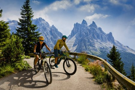 Photo for Couple mountain bike riders on electric bike, e-mountainbike rides up mountain trail. Woman and Man riding on bike in Dolomites mountains landscape. Cycling e-mtb enduro trail track. Outdoor sport activity. - Royalty Free Image
