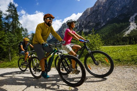 Photo for Tourist cycling in Cortina d'Ampezzo, stunning rocky mountains on the background. Family riding MTB enduro flow trail. South Tyrol province of Italy, Dolomites. - Royalty Free Image