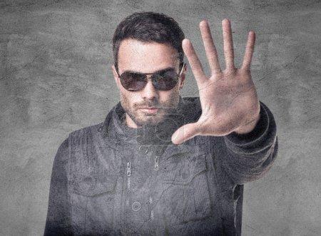Foto de Hombre guapo en gafas de sol muestra la señal de parada. Sobre fondo vintage gris - Imagen libre de derechos