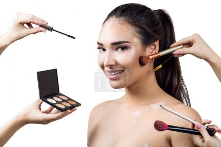 Photo for Beauty portrait of young woman with vitilio among hands with make-up brushes. Isolated over white background - Royalty Free Image