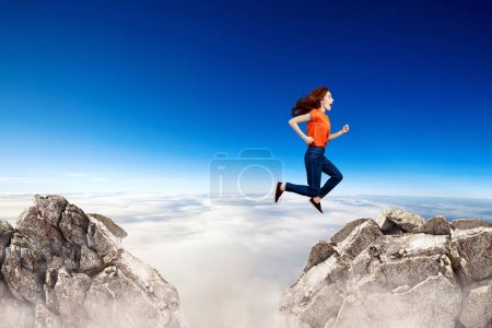 Photo for Redhead woman jumps through the gap between hills over cliff on blue sky background. - Royalty Free Image