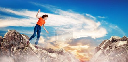 Photo for Redhead woman falling down between hills on cliff on blue sky background. - Royalty Free Image