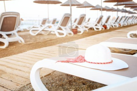 Photo for View on many deck chairs with summer white hat on one of them. Stands on the sandy beach with beach umbrellas. - Royalty Free Image