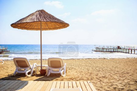 Photo for Sea sandy beach with the two deck chairs and the beach umbrella. - Royalty Free Image