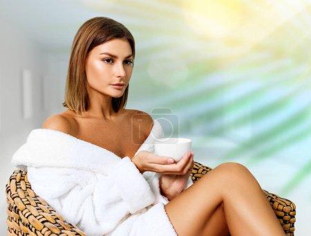 Photo pour Belle femme en peignoir assis sur la chaise et boire du thé dans le salon de spa . - image libre de droit