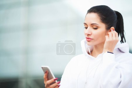 Fitness. Woman listening music on phone while exer...