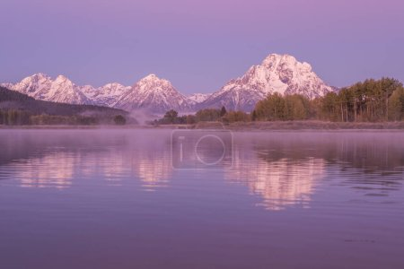 a scenic autumn reflection of the Tetons at sunrise