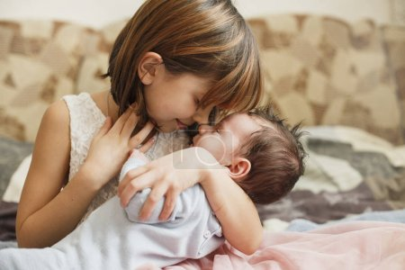 Photo for Little sister hugging her newborn brother. Toddler kid meeting new sibling. Cute girl and new born baby boy relax in a home bedroom. Family with children at home. - Royalty Free Image