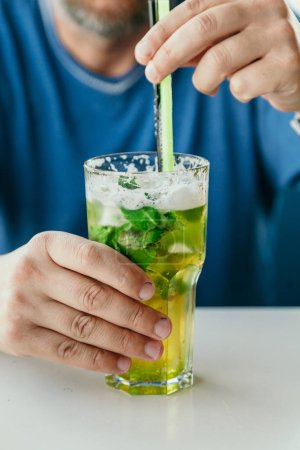 mans hand holds a tall transparent glass with a mojito cocktail and a straw on the tabl