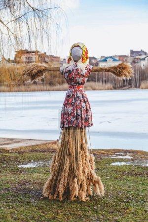 Photo pour Vacances slaves de la fin de l'hiver. Une grande poupée Shrovetide en paille dans la robe et l'écharpe d'une femme se tient sur l'interdiction de la rivière - image libre de droit