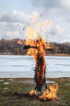 Photo pour Vacances slaves de la fin de l'hiver. Une grande poupée Shrovetide de paille brûle sur la rive de la rivière. La fumée noire est visible - image libre de droit