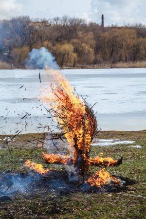 Photo pour Vacances slaves de la fin de l'hiver. Sur le rivage d'une rivière gelée, les restes d'une effigie de paille de la semaine des crêpes - image libre de droit
